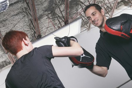 sport, fitness, lifestyle and people concept - woman with personal trainer boxing punching bag in gym photo
