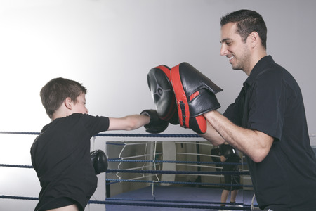 coach sport: A coach with a child learning boxe