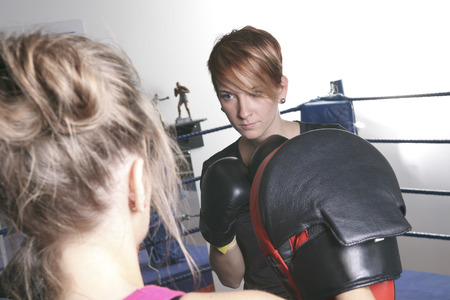 sport, fitness, lifestyle and people concept - woman with personal trainer boxing punching bag in gym 版權商用圖片