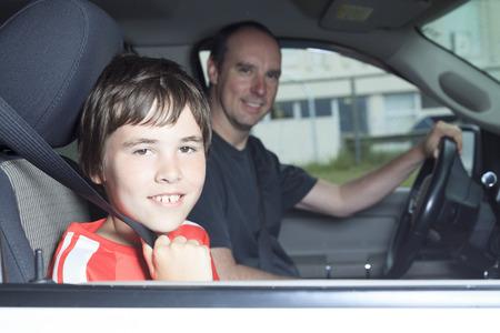 彼の父の車で微笑む少年の肖像画 写真素材