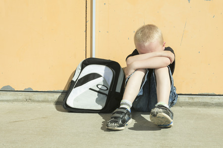 harassment: A boy bullying in school playground. very sad! Stock Photo