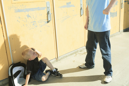 bullying: A boy bullying another in school playground