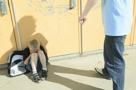 school playground: A boy bullying another in school playground