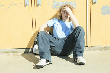 lonely boy: sad lonely boy in the school playground