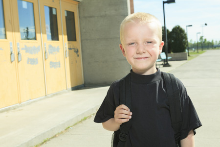 5 6 years: A boy on the playground of his school with a backpak