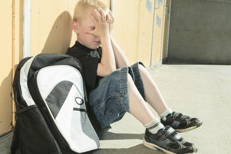 school playground: A very sad boy bullying in school playground.