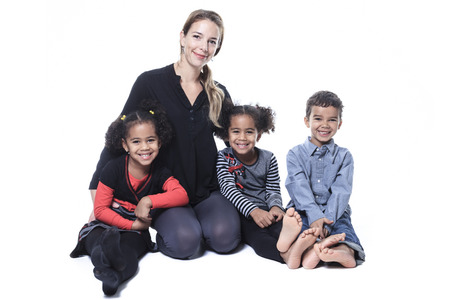 A family sitting on the floor of a photography studio photo