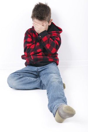 6 7 year old: A sad young boy sit on white background Stock Photo