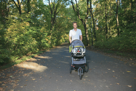 30 years old man: A 30 years old man with a stroller walking in the park
