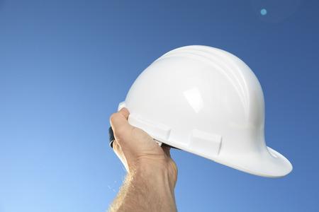 A hand holding a foreman helmet over the sky photo