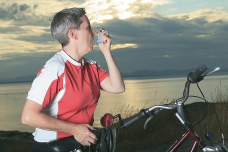 inhalator: A senior woman with asthma inhalator on bike at the sunset.