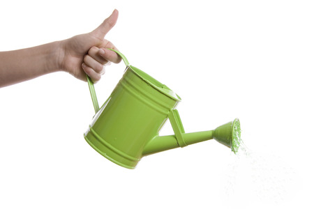 a hand with a watering can over a white background photo