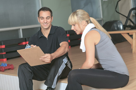 trainer: gym woman personal trainer man with weight training equipment Stock Photo