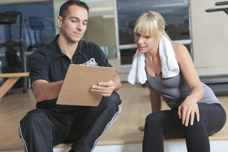 gym woman personal trainer man with weight training equipment Standard-Bild