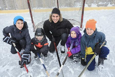 hockey sobre hielo: Una familia que juega en la pista de patinaje en invierno.