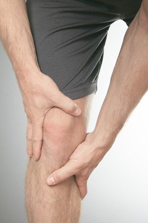 knee cap: Man with both palm around knee cap to show pain and injury on knee area.