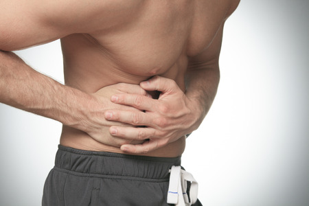 constipation symptom: A men holding hands on his stomach Stock Photo