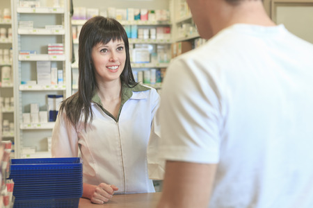 A Pharmacist helping customer at counter place photo