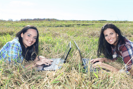 Young beautiful girls with laptop in a field photo