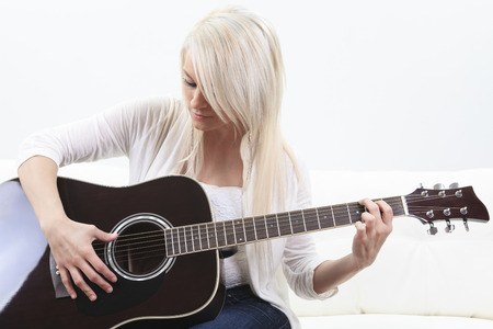 linda: beautiful young woman on the couch with a guitar