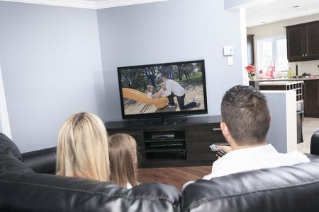 家庭で一緒にテレビを見ている若い家族 写真素材