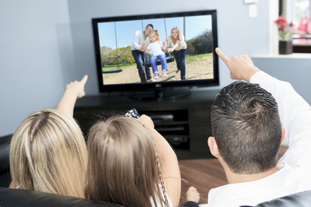 screen tv: A Young family watching TV together at home Stock Photo