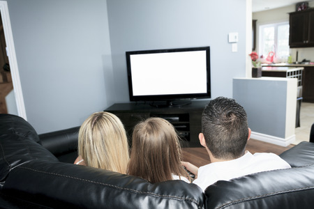 A Young family watching TV together at home Stock Photo