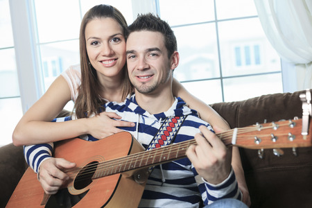 serenading: A Handsome man serenading his girlfriend with guitar at home in the living room