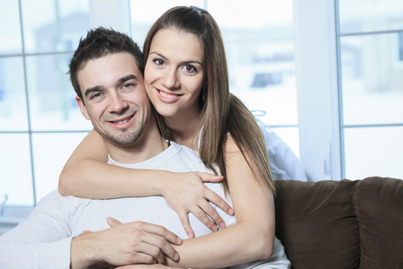 couple on couch: An happy couple at home relaxing in sofa
