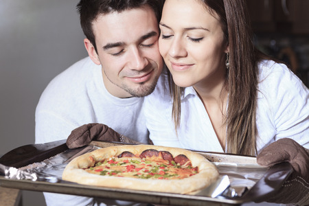 A Happy young couple eating pizza at the kitchen photo