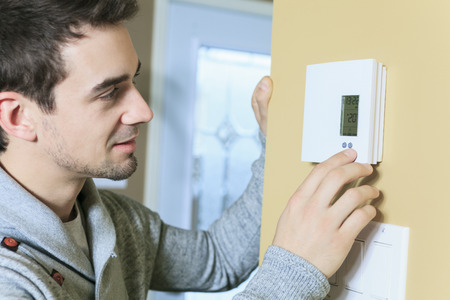 conservation: A man set the thermostat at house.