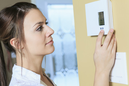 thermostat: A woman set the thermostat at house.