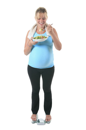A pregnant woman wearing in training with a salad photo