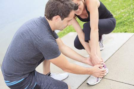 sprain: Injury - sports woman with twisted sprained getting help from man touching her ankle.
