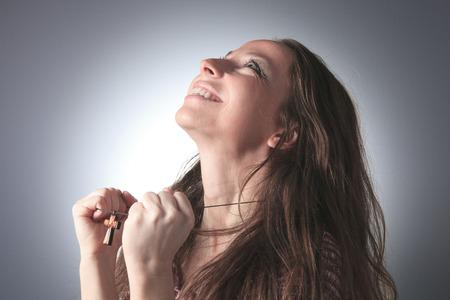 A nice woman praying on grey background photo