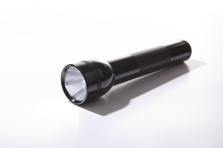 A black flashlight over a gray background on the floor photo