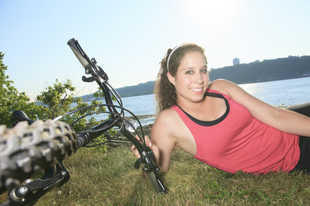 A young woman with bicycle and enjoying the summer photo