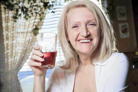 台所のテーブルに引退した女性 写真素材