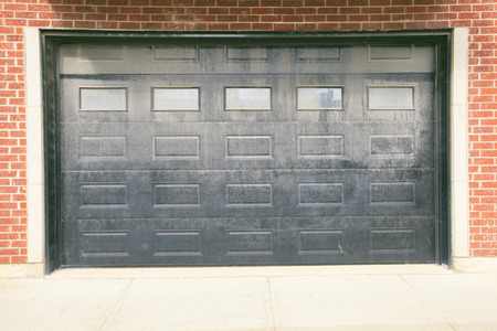 Big garage with dark doors, brick wall photo