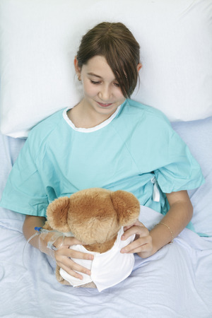 Little girl in hospital bed with teddy bear photo
