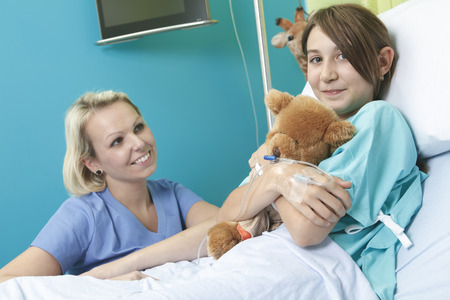 Little girl in hospital bed with the nurse photo