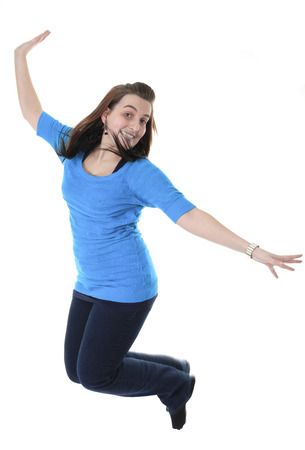 Full length studio photo of attractive woman jumping in air with arms extended. White background. Stock Photo