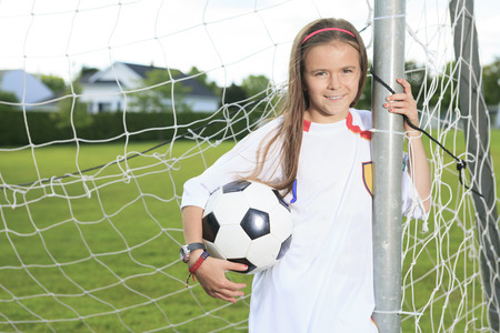 girl kick: Kid play soccer on a field