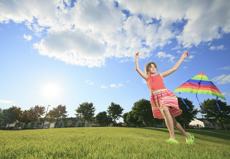 A Little girl running in park with a kite photo