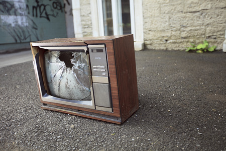 cracked glass: An old broken TV left on the street.