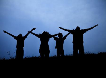 family praying: La familia de tres personas acoge con beneplácito el sol del atardecer.