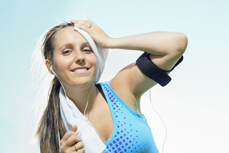 A woman cleaning her sweat with a towel Stock Photo