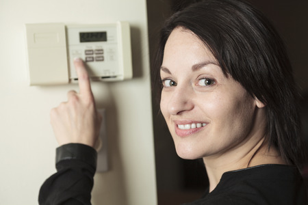 adult footprint: A woman in house who set is thermostat.