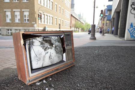 technology symbols metaphors: An old broken TV left on the street.