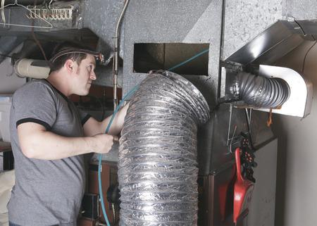 Un homme de nettoyage de ventilation au travail avec l'outil